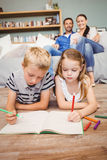 Children drawing on book while parents looking at them Stock Photos