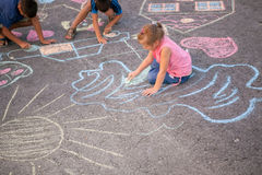 Children drawing with chalk on asphalt Royalty Free Stock Photography