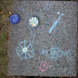 Children drawing with chalk on asphalt. Royalty Free Stock Images