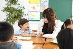 Children drawing in the classroom and teacher near by. Happy children drawing in the classroom and teacher near by Stock Image