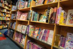 Children drawing and coloring books on shelves in a bookstore for sale. Library kids books section. Variety of Books For Sale On