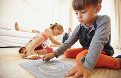 Children drawing and coloring at home. Little boy drawing and coloring while sitting on floor in living room. Children on floor painting with parents sitting on Royalty Free Stock Photo