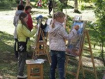 Children drawing on easels outdoor. Children drawing on wooden easels in the park Stock Images