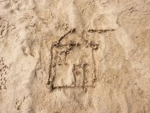 Children drawing of family house in sand on beach of bay. Open window and open doo Stock Images