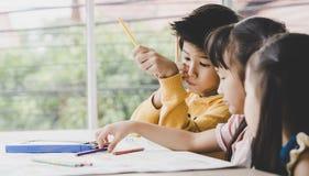 Children are drawing in kindergarten art classroom. Asian children are drawing in kindergarten art classroom stock photos