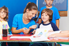 Children drawing with nursery teacher in kindergarten Stock Photography