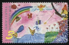 Children drawing of rainbow. RUSSIA KALININGRAD, 2 JUNE 2016: stamp printed by Thailand, shows children drawing of rainbow, birds, field near the river, circa stock photos