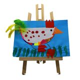 Children drawing representing a chicken with colored feathers on blue paper displayed on a wooden easel. stock images