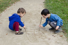 Children drawing into sand Stock Photography