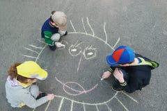 Children is drawing sun on asphalt in park. Stock Photo