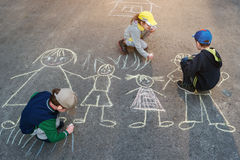 Children is drawing sun on asphalt in the park. Stock Photo