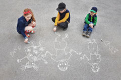 Children is drawing sun on asphalt in spring park. Royalty Free Stock Images