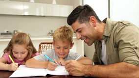 Children drawing with their dad at the table stock video
