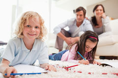 Children drawing while their parents are in the background Stock Images
