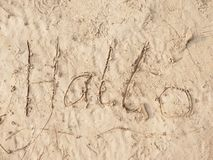 Children drawing of word hallo in sand on beach of bay. Letters written in sand. Stock Photos