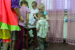Children drawings around the table in the kindergarten. 2019.01.22, Moscow, Russia. Children drawings around the table in the kindergarten. Group of funny boys royalty free stock photography