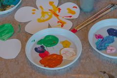 Children drawings flower, paints and brushes stock photo