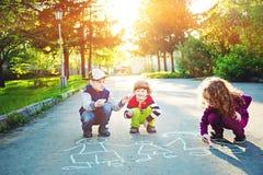 Children draws on asphalt in summer park. Royalty Free Stock Photos
