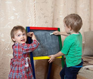 Children draws on blackboard with chalk. Children draws on the blackboard with chalk at home stock photos