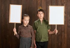 Children are dressed in retro military uniforms. They`re holding blank posters for veterans portraits. stock photos