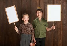 Children are dressed in retro military uniforms. They`re holding blank posters for veterans portraits. stock photo