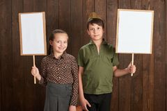 Children are dressed in retro military uniforms. They`re holding blank posters for veterans portraits. royalty free stock image