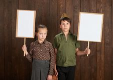 Children are dressed in retro military uniforms. They`re holding blank posters for veterans portraits. stock image