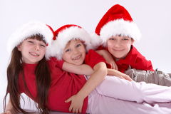 Children dressed in santa hats Stock Photos