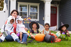 Children Dressed In Trick Or Treating Costumes On Lawn Royalty Free Stock Photos
