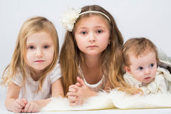 Children dressed in white lying on fur Stock Images