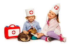 Children dressed at whites bandage paw to a cat Stock Photography