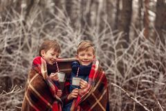 Children drink hot chocolate under warm blanket in winter forest. Christmas vacation. Children drink hot chocolate under warm blanket in winter forest stock photo