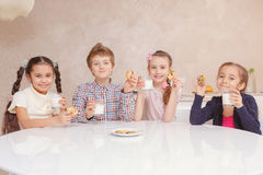 Children drink milk with cookies Royalty Free Stock Photo