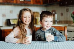 Children drink milk and have fun in the kitchen at the morning. Sister and brother holding a full glasses of milk stock image