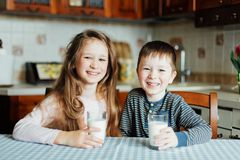 Children drink milk and have fun in the kitchen at the morning. Sister and brother prepare cocoa stock photo