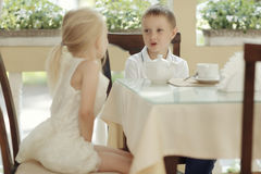 Children drink tea in cafe Stock Images