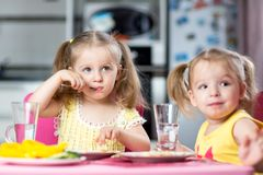 Children drinking and eating at daycare Stock Photo