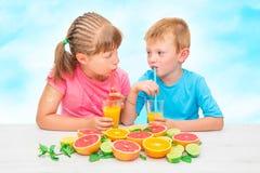 children drinking juice frome fresh orange and grapefruit stock photos