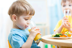 Children drinking juice at nursery or at home Stock Photos