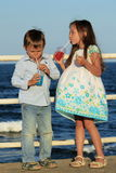Children drinking juice. Two brothers drinking colored juice by the sea side Stock Images