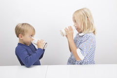 Children drinking milk while looking at each other Royalty Free Stock Image