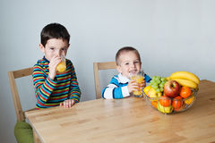 Children drinking orange juice. Children sitting at the table and drinking the orange juice Stock Image