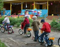 Children driving on designer bicycles and scooters in Russia. Children driving on designer bicycles and scooters in kindergarten in summer, Russia Stock Photo