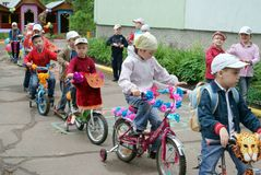 Children driving on designer bicycles and scooters in Russia. Children driving on designer bicycles and scooters in kindergarten in summer, Russia Royalty Free Stock Photography