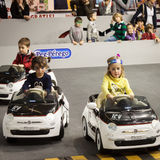 Children driving electric cars at G! come giocare in Milan, Italy Stock Image