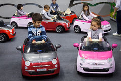 Children driving electric cars at G! come giocare in Milan, Italy Stock Photography