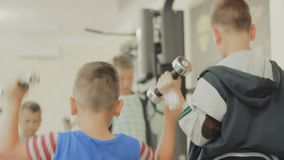 Children with dumbbells in the gym. Little Boy training with dumbbells together with coach at fitness center. children care about their body, figure, appearance stock video