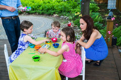Children Dyeing their Easter Eggs Outside. A family picture of children having fun painting and decorating eggs outside.  Children dye their Easter eggs as the Stock Photos
