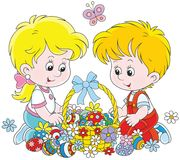 Children with an Easter basket. A Little girl and a little boy sitting around a decorated basket of colorfully painted Easter eggs and flowers Stock Photo