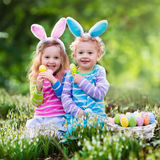 Children on Easter egg hunt. Kids on Easter egg hunt in blooming spring garden. Children with bunny ears searching for colorful eggs in snow drop flower meadow royalty free stock image